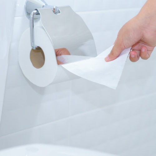 Close up of A woman hand using toilet paper in white and clean toilet room